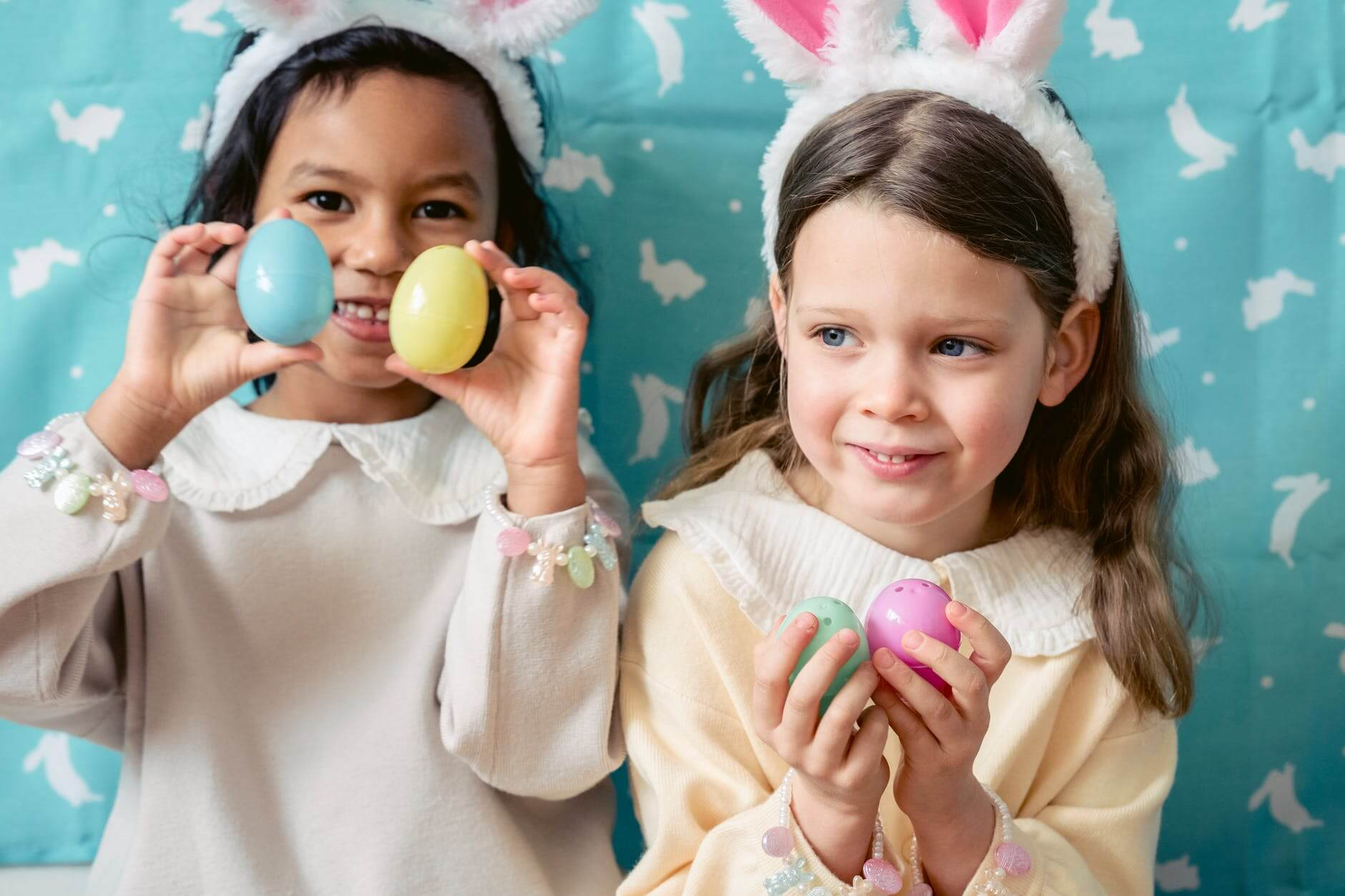 glad diverse girls playing with toy eggs